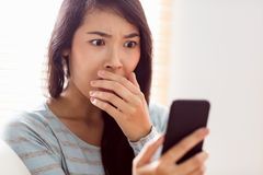 Asian woman reading shocking text Stock Photos