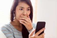 Asian woman reading shocking text Stock Photos