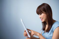 Asian woman reading a tablet pc Royalty Free Stock Photography