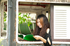 Asian woman reading at window of old train room . Royalty Free Stock Images