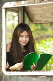 Asian woman reading at window of old train room . Stock Photography