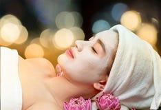 Asian woman receiving clay facial mask in spa beauty salon stock photo