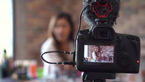 Asian woman recording video about cosmetics with DSLR on tripod