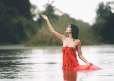 An Asian woman in red bathrobe is enjoying rain and nature in th. E wild royalty free stock photos