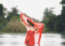An Asian woman in red bathrobe is enjoying rain and nature in the wild.  royalty free stock photography