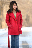 Asian Woman in Red Coat. Walking outside in the snow Royalty Free Stock Images