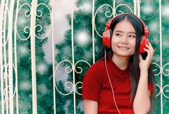 Asian woman in red headphones enjoying music stock images