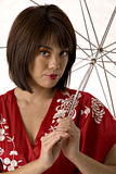 Asian woman in red kimono. Young asian woman in red and white kimono holding umbrella Stock Image