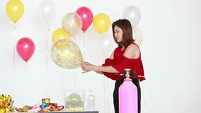 Asian woman in red shirt using balloon pump to blowing glitter balloon, colorful balloons behind her, concept for party. stock video