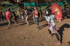 An asian woman with a red umbrella and a white cat mask dances on the Lost Theory psytransce music festival