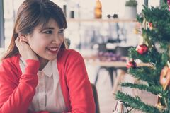 Asian woman relax & smile at home. girl with christmas tree. xma Royalty Free Stock Image