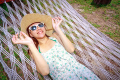 Asian woman relaxing on the beds beside garden Royalty Free Stock Images