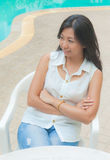 An Asian woman relaxing on a chair beside swimming pool Royalty Free Stock Photo