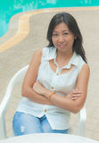 An Asian woman relaxing on a chair beside swimming pool Stock Images
