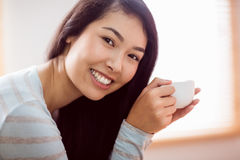 Asian woman relaxing on couch with coffee Stock Photos