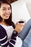 Asian woman relaxing on couch with coffee Royalty Free Stock Photo