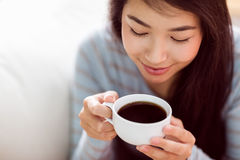 Asian woman relaxing on couch with coffee Royalty Free Stock Photography