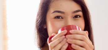 Asian woman relaxing on couch with coffee. At home in the living room Stock Photography
