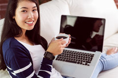 Asian woman relaxing on couch with coffee using laptop Royalty Free Stock Photography