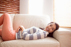 Asian woman relaxing on couch. At home in the living room Stock Image