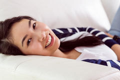Asian woman relaxing on couch. At home in the living room Royalty Free Stock Photo
