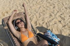 Asian woman relaxing and listening to music via headphone form smartphone, lying on chair on the beach. Travel of summer vacation royalty free stock photo