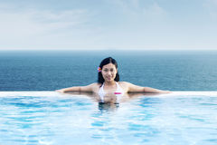 Asian woman relaxing at luxury pool by the beach royalty free stock photography