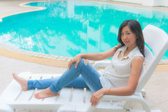 An Asian woman relaxing on a pool chair Stock Photography