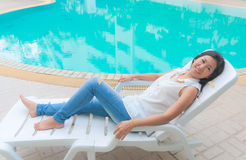 An Asian woman relaxing on a pool chair Royalty Free Stock Photos
