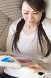 Asian woman relaxing on the sofa Royalty Free Stock Photography