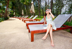 Asian woman relaxing on sun beds beside garden Stock Photos