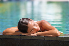 Asian woman relaxing sunbathing - pool spa retreat royalty free stock images