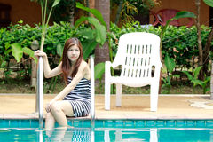 Asian woman relaxing beside the swimming pool Royalty Free Stock Photo