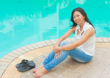 An Asian woman relaxing beside a swimming pool Stock Photography
