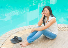 An Asian woman relaxing beside a swimming pool Royalty Free Stock Photo