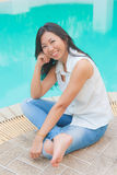 An Asian woman relaxing beside a swimming pool Royalty Free Stock Photography