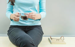 Asian woman rest for drink coffee in transparent glass cup in her hand in her free time in the room with wooden desk and frosted g Royalty Free Stock Image