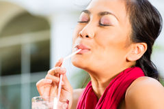 Asian woman in restaurant drinking Royalty Free Stock Photography
