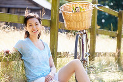 Asian Woman Resting By Fence With Old Fashioned Cycle Stock Photos