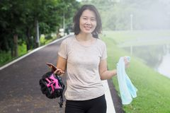 Asian Woman Ride Bicycle. Asian Sport Woman with Cycling Helmet Acting near the Lagoon Royalty Free Stock Photography