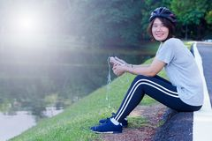 Asian Woman Ride Bicycle. Asian Sport Woman with Cycling Helmet Acting near the Lagoon Stock Image