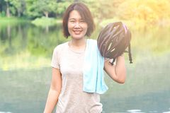 Asian Woman Ride Bicycle. Asian Sport Woman with Cycling Helmet Acting near the Lagoon Royalty Free Stock Photo