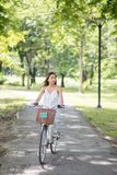 Asian woman ride bicycle in summer park. Asian Beautiful happy  woman looking at summer garden while  riding a bicycle at park with foliage bokeh background Stock Image