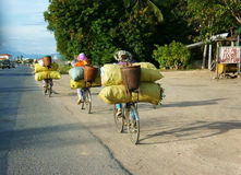 Asian woman ride cycle, transfer overload. PHAN RANG, VIET NAM- OCT 22: Group of Asian woman ride cycle on highway, women transfer overload bag,  trafiic in Stock Photo