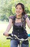 Asian woman riding bicycle Royalty Free Stock Image