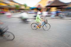 Person riding blue bike in Hoi An, Vietnam, Asia. Asian woman riding blue bike. Person on bicycle. Crossroad of Hoi An in Vietnam, Asia. Blur motion of busy Stock Photos