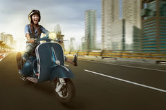 Asian woman riding scooter and wearing helmet Stock Photography