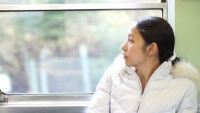 Asian woman riding in train in sunny day stock video