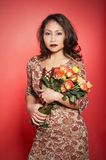 Asian woman with roses. Portrait of a woman with roses. Asian. The background is red Stock Photos