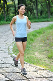 Asian woman runner running outdoor. In path Stock Image